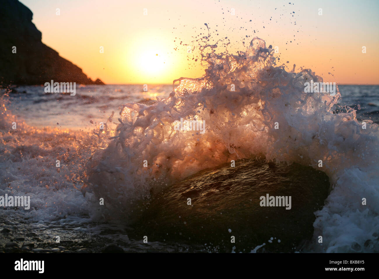 At sunrise, waves crash on the stone - Stock Image