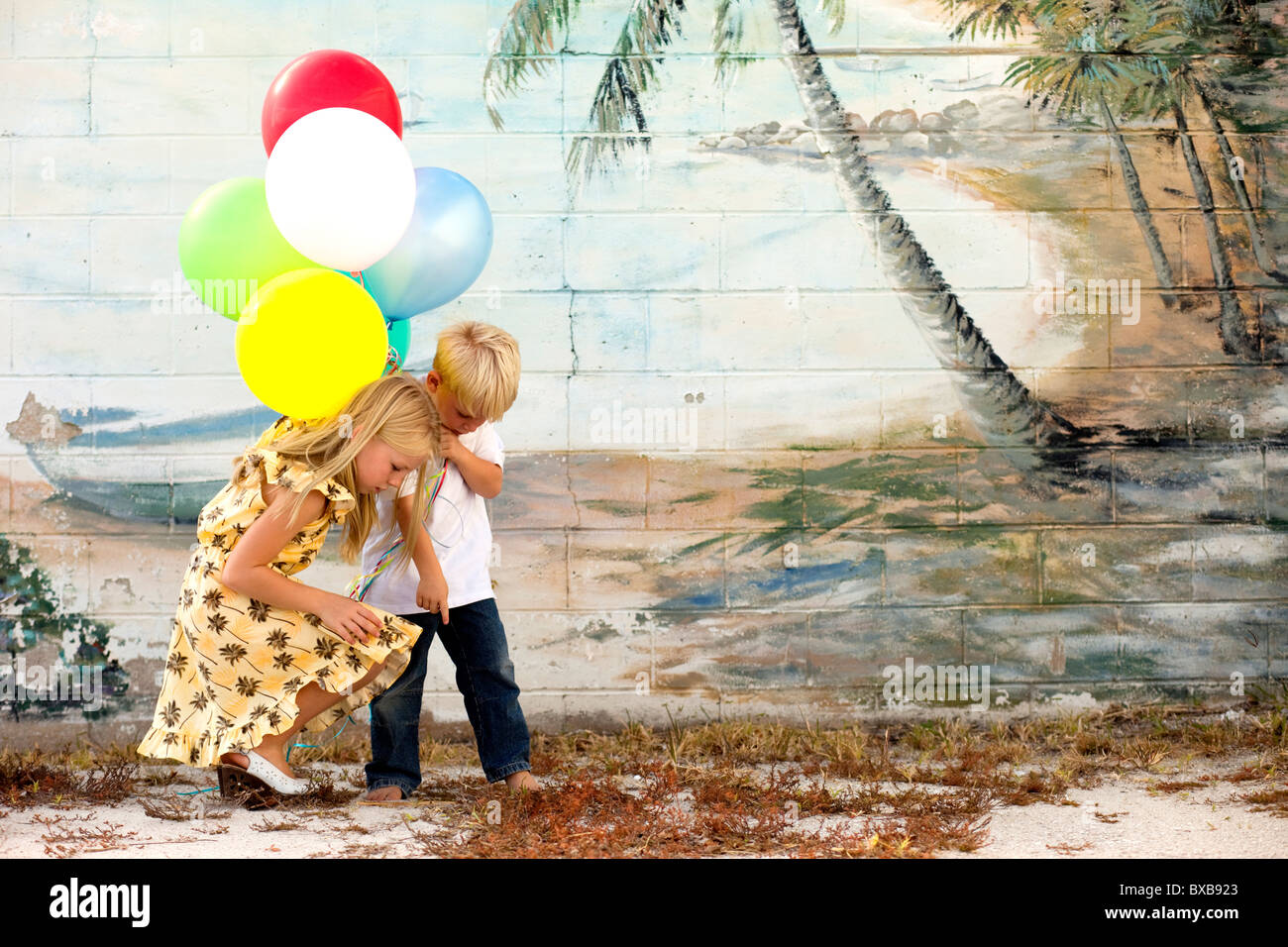 Young boy and girl with balloons looking at ground - Stock Image