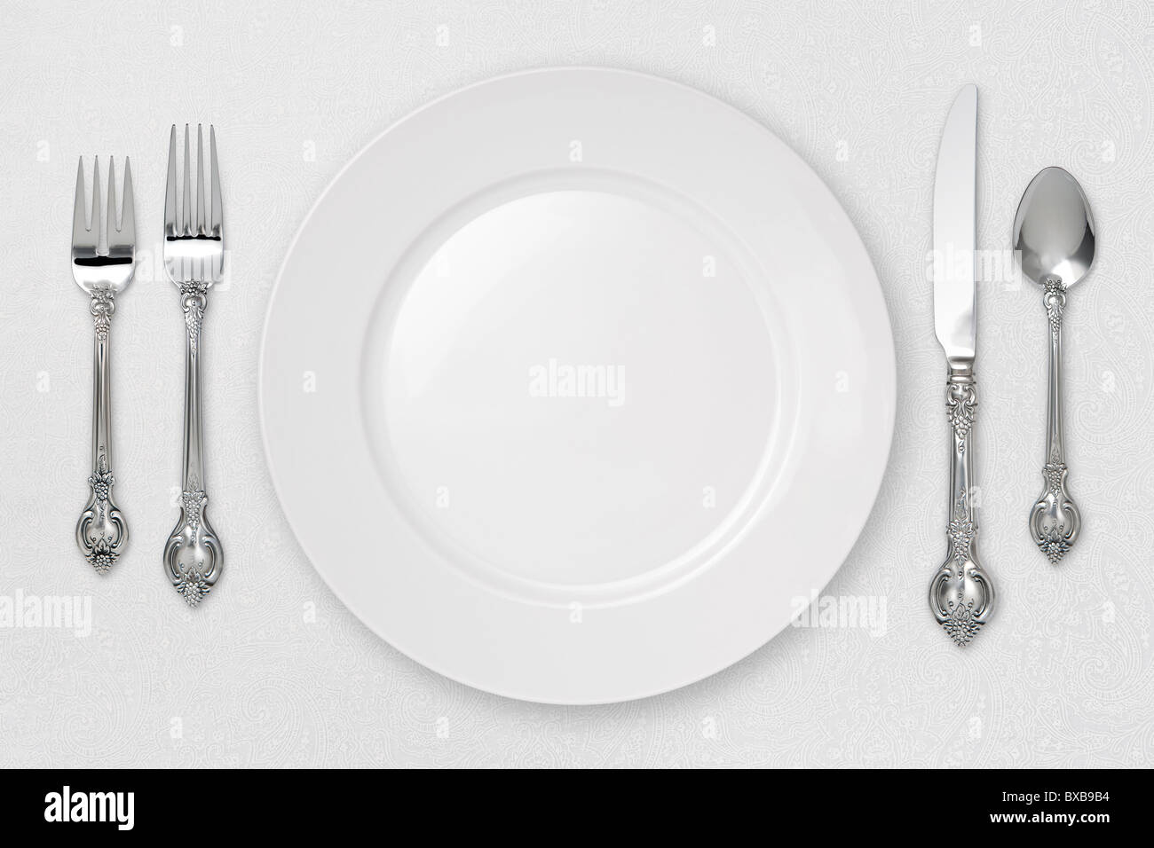 White Place Setting on tablecloth. - Stock Image