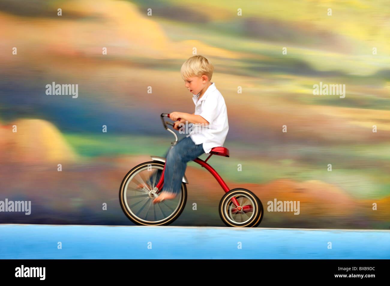 Young boy riding tricycle against colorful sky with clouds - Stock Image