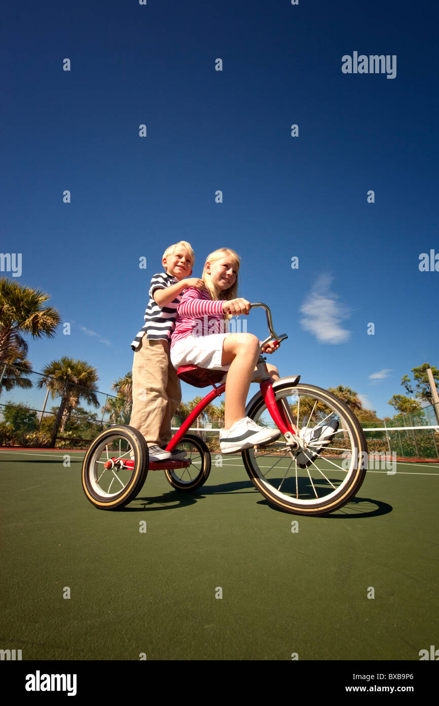 Boy and girl riding tricycle together - Stock Image