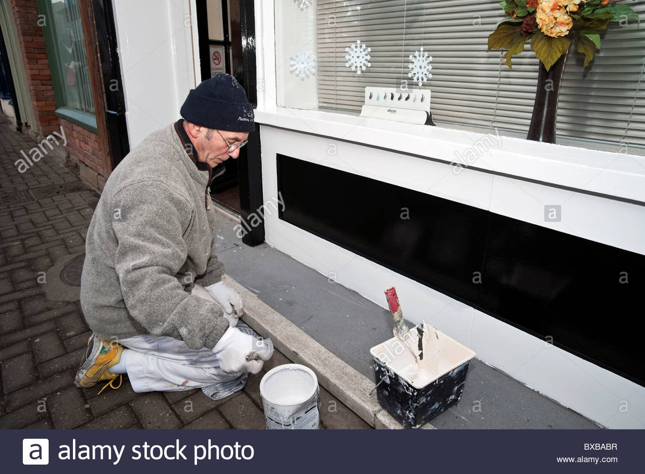 Painter & decorator at work painting a storefront, UK. Painter working outside on the exterior of a shop. - Stock Image