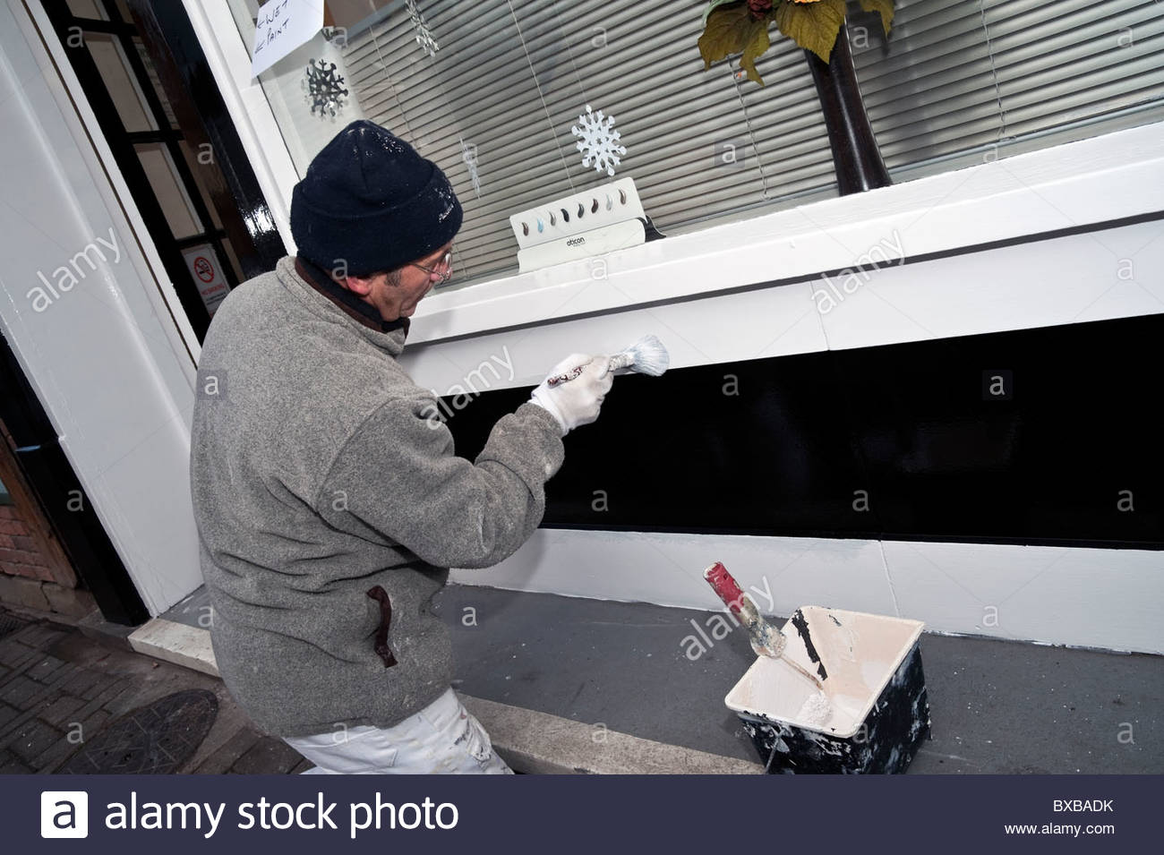 Painter & decorator at work painting a storefront, UK. Painter working outside on the exterior of a shop. Wet - Stock Image