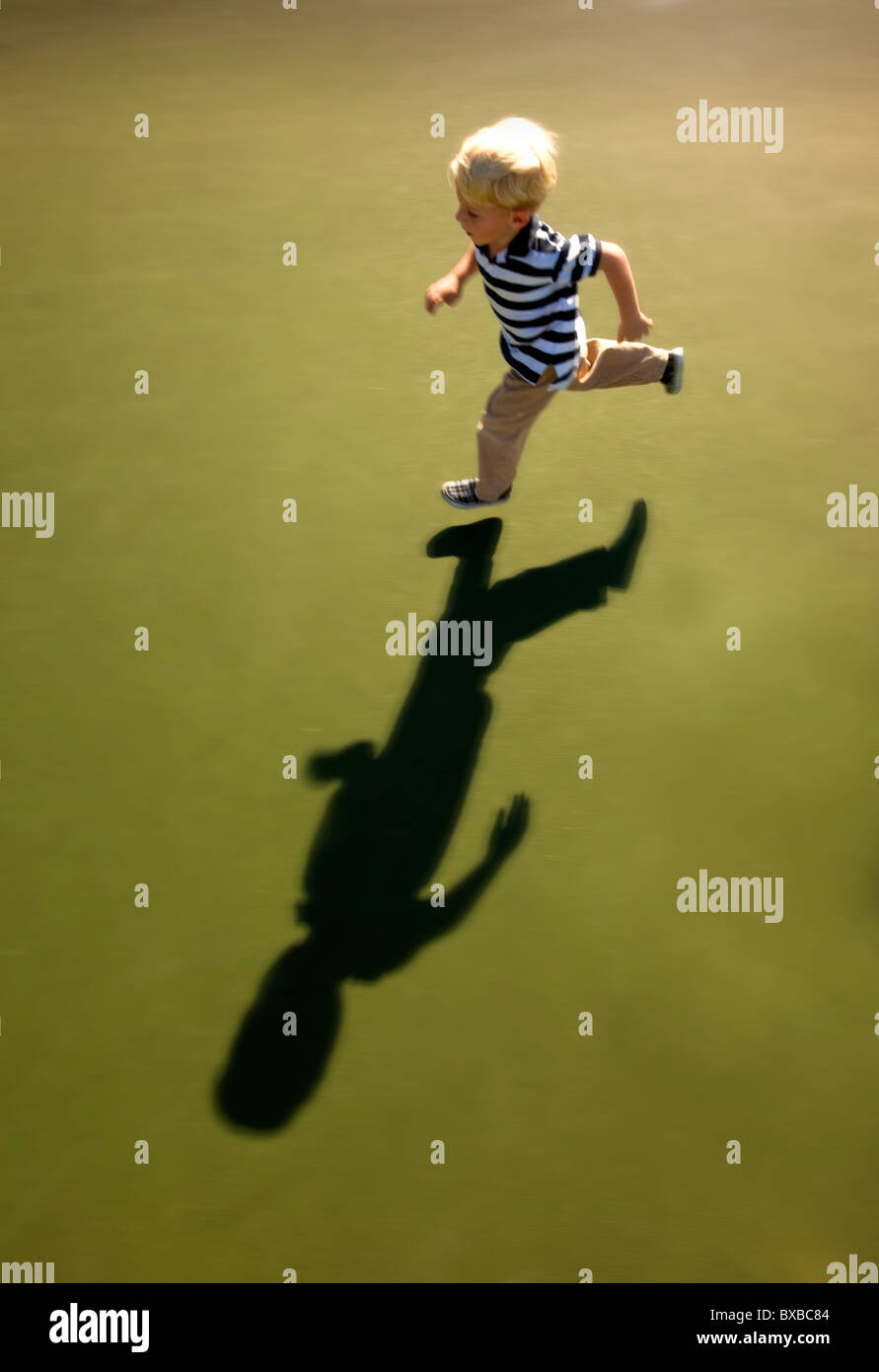 Young boy running with shadow - Stock Image