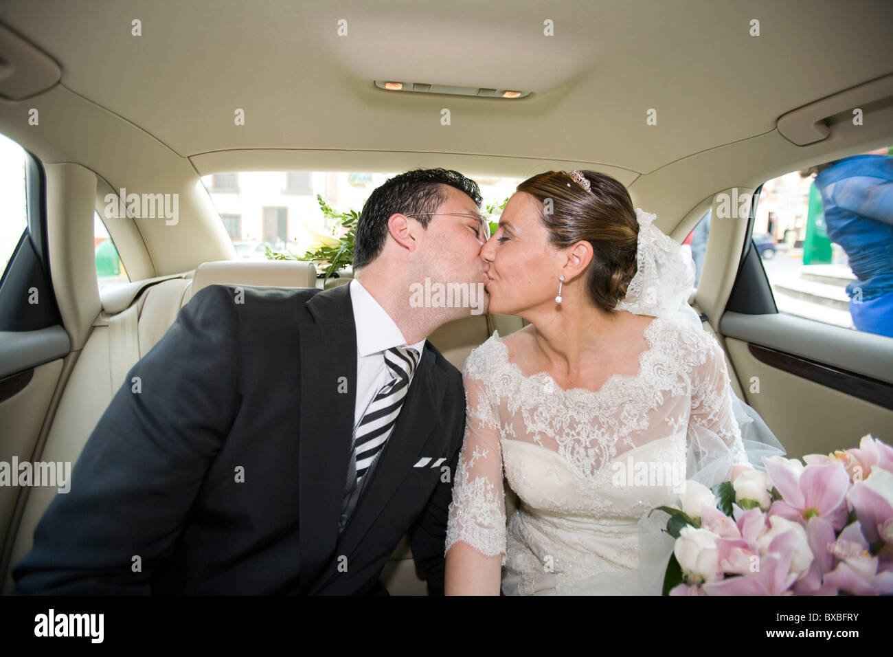 A newly wed couple kissing in a car - Stock Image
