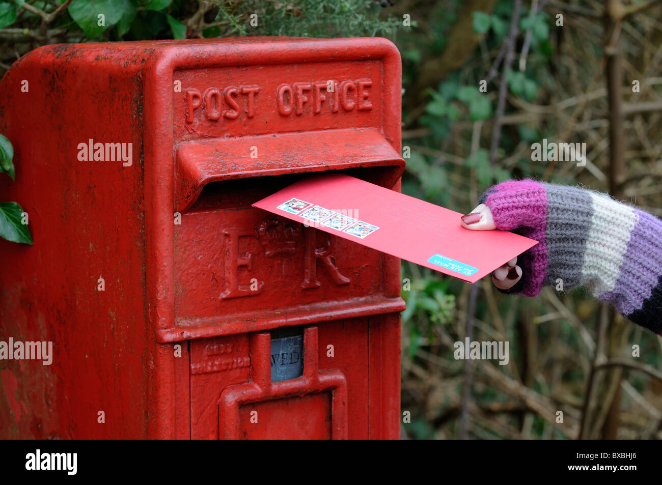 Woman posting Christmas greetings cards in a Royal Mail letterbox - Stock Image