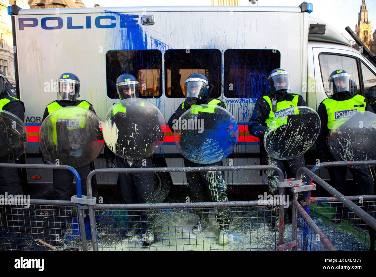 Riot police splattered with paint thrown by protesters during Tuition Fees demonstration in Parliament Square - Stock Image