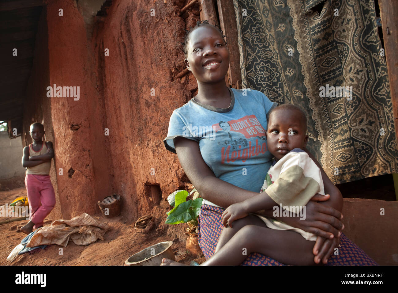 A woman holds her child outside her home in a slum in Jinja, Uganda, East Africa. Stock Photo
