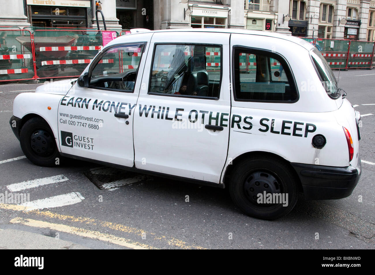 Taxi with advertising, earn money while others sleep, in London, England, United Kingdom, Europe - Stock Image