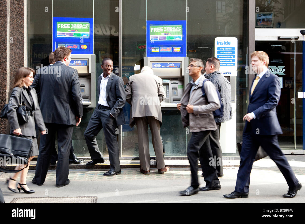 Passers-by at the cash machine of the Halifax Bank in London, England, United Kingdom, Europe - Stock Image