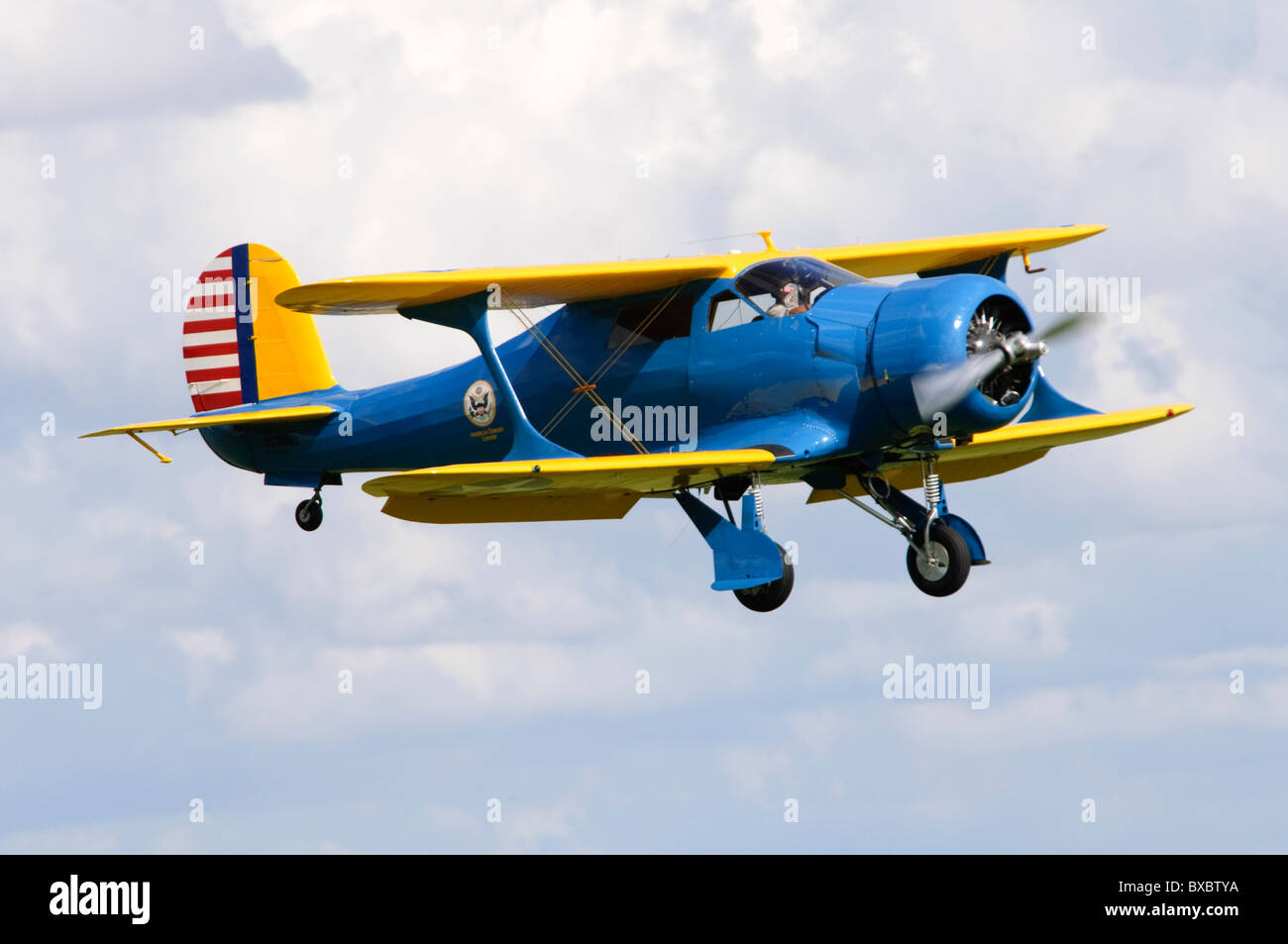 Beech YC-43 Traveller (Staggerwing) biplane making a flypast at Duxford Flying Legends Airshow - Stock Image