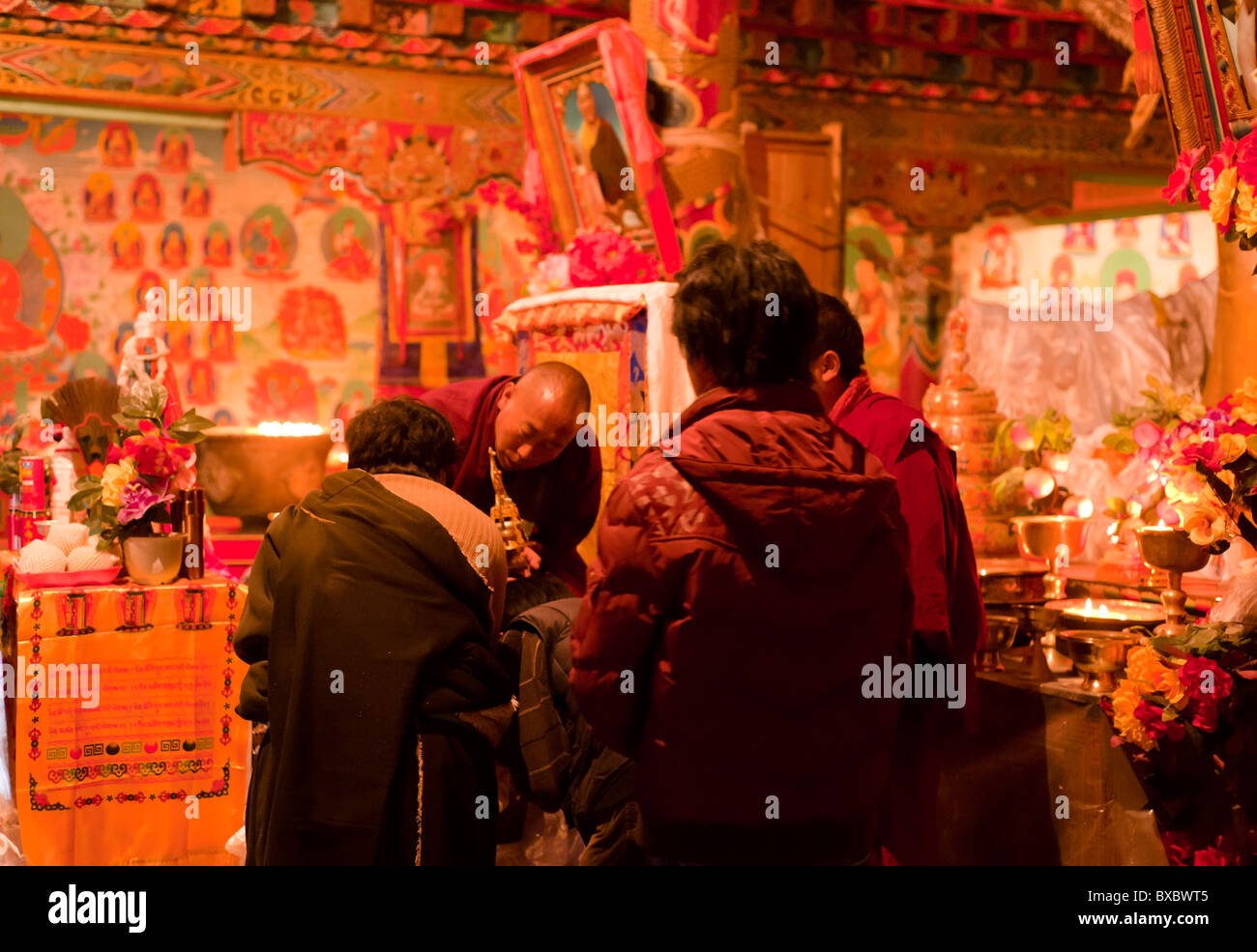 A Tibetan monk blesses lamaist adherents during a ceremony in Tagong Temple, Sichuan province, China - Stock Image