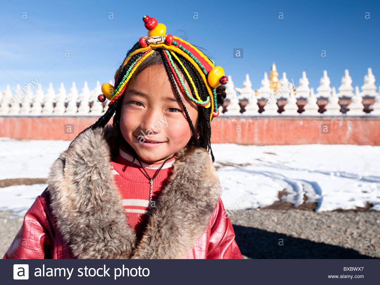Unidentified tibetan girl in Tagong. She wears a feathered jacket as here temperatures in easily drop down below Stock Photo