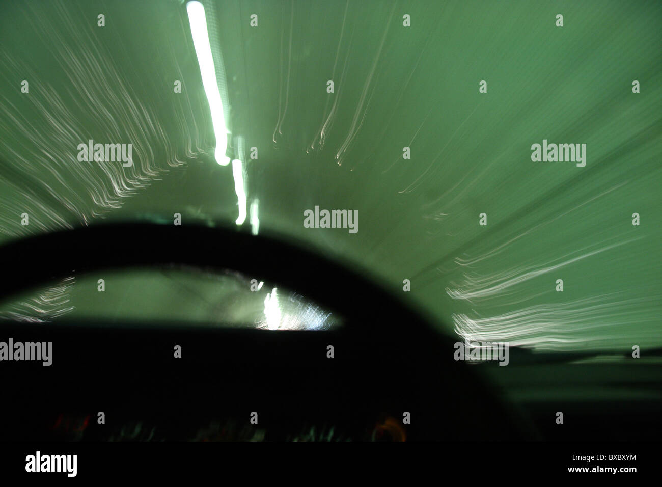 Blurred motion of car moving through a tunnel with steering wheel in foreground Stock Photo