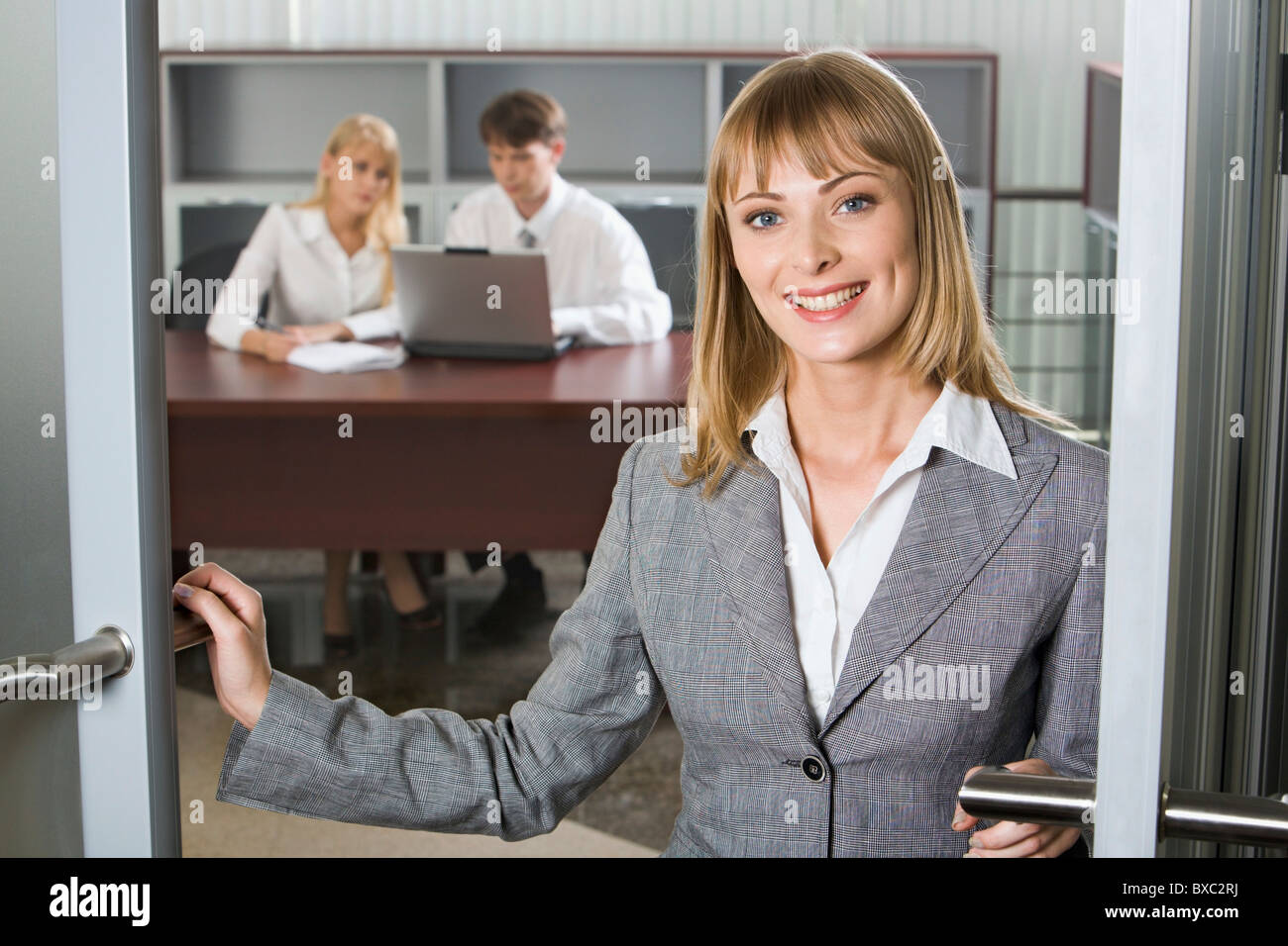 Svelte young woman in gray business suit is touching the doors and two young businesspeople on the background working - Stock Image
