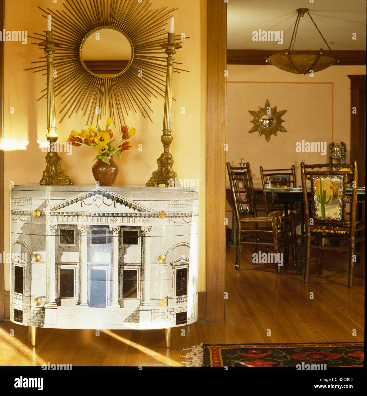 Gold sunburst mirror above Fornasetti cabinet with tall candlesticks in traditional dining room - Stock Image