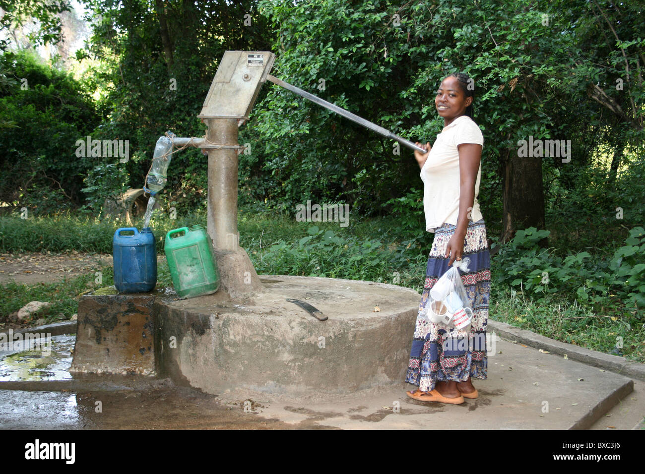 Smiling Ethiopian Woman Pumping Water From A Well - Stock Image