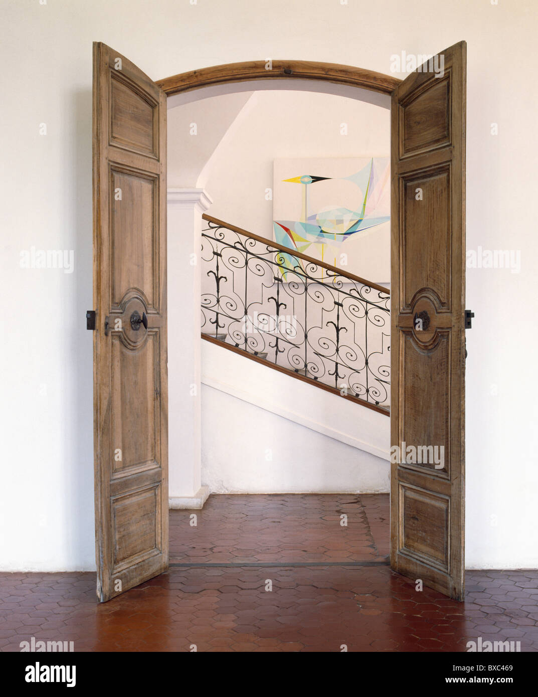 double door open. Old Carved Wood Double Doors Open In French Country Hall With View Of Wrought Iron Banisters On Staircase Door