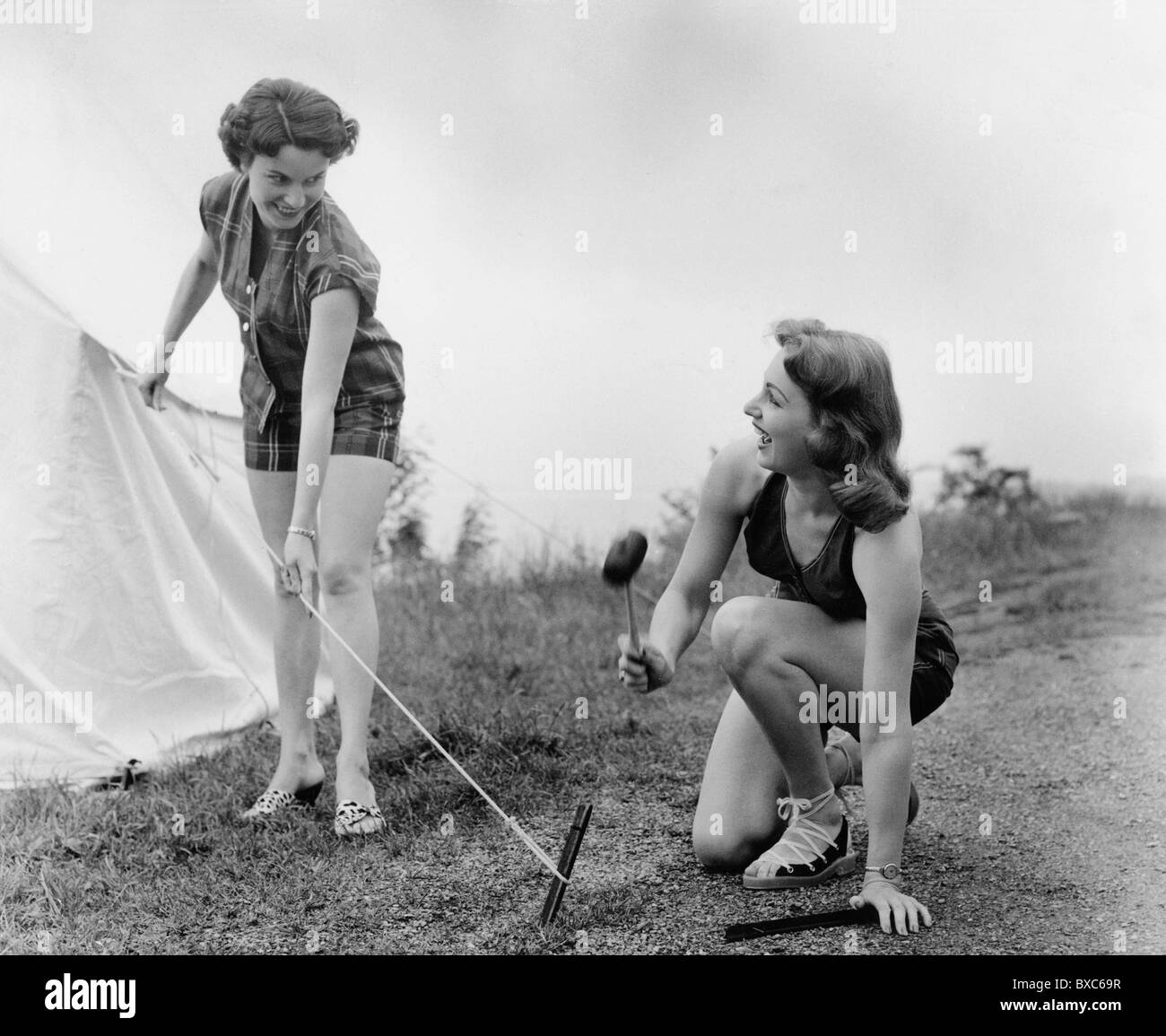 tourism, camping, two women erecting a tent, hitting tent peg in the ground, 1955, Additional-Rights-Clearences - Stock Image