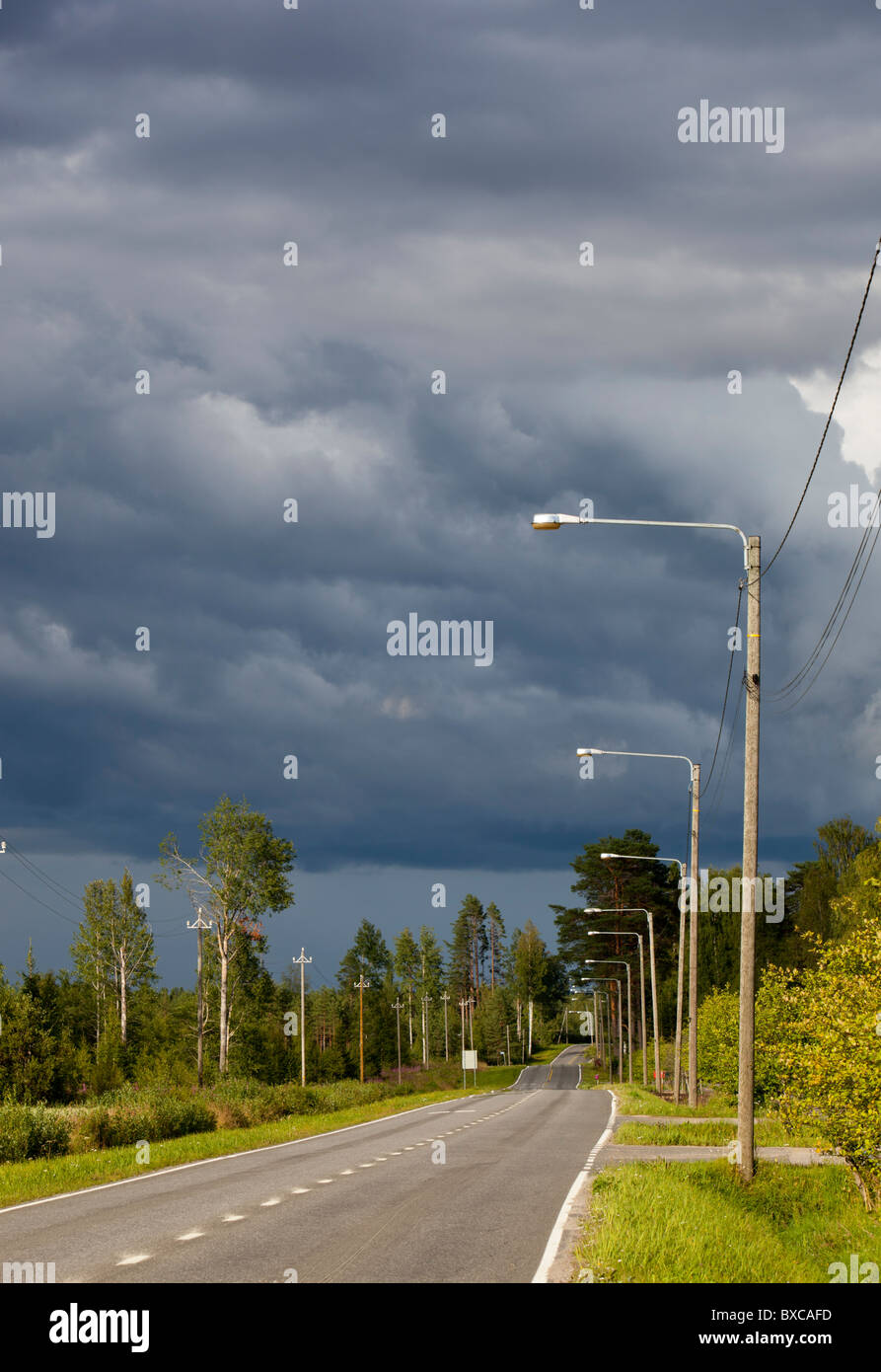 Empty road at countryside and rising thunderstorm clouds , Finland - Stock Image
