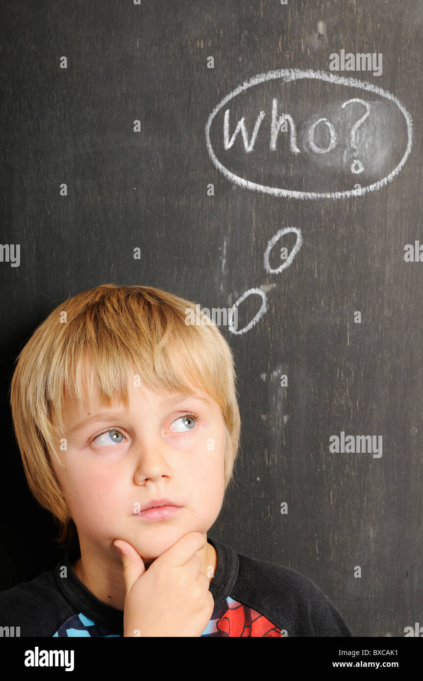 Stock photo of a young boy in fornt of a blackboard with chalk thought bubbles spelling the word WHO. - Stock Image