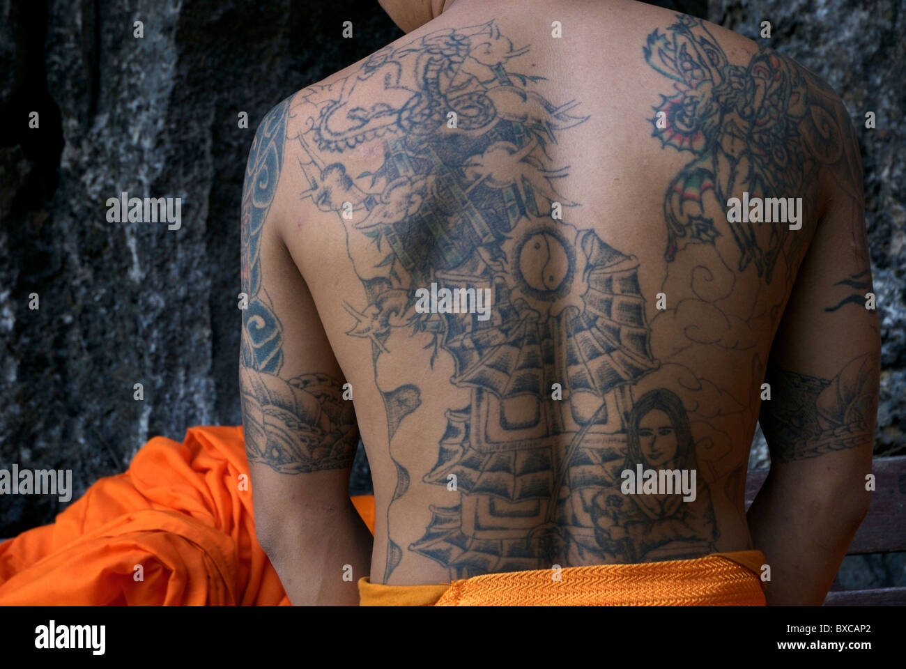 A young monk in Vang Vieng has many Tättoos on the back Stock Photo