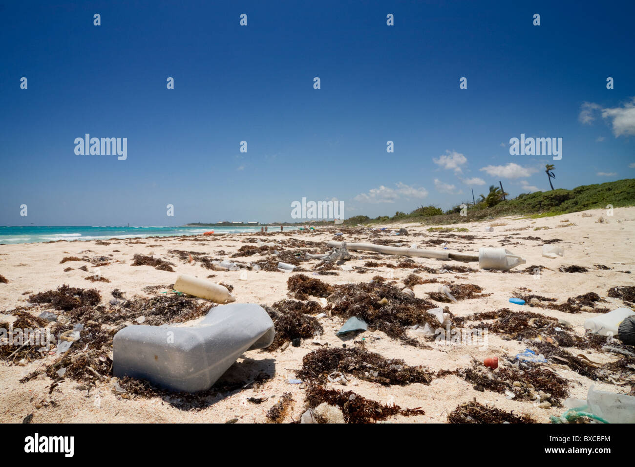 Close up view of washed up garbage on a beach right next to a vacation resort. Stock Photo