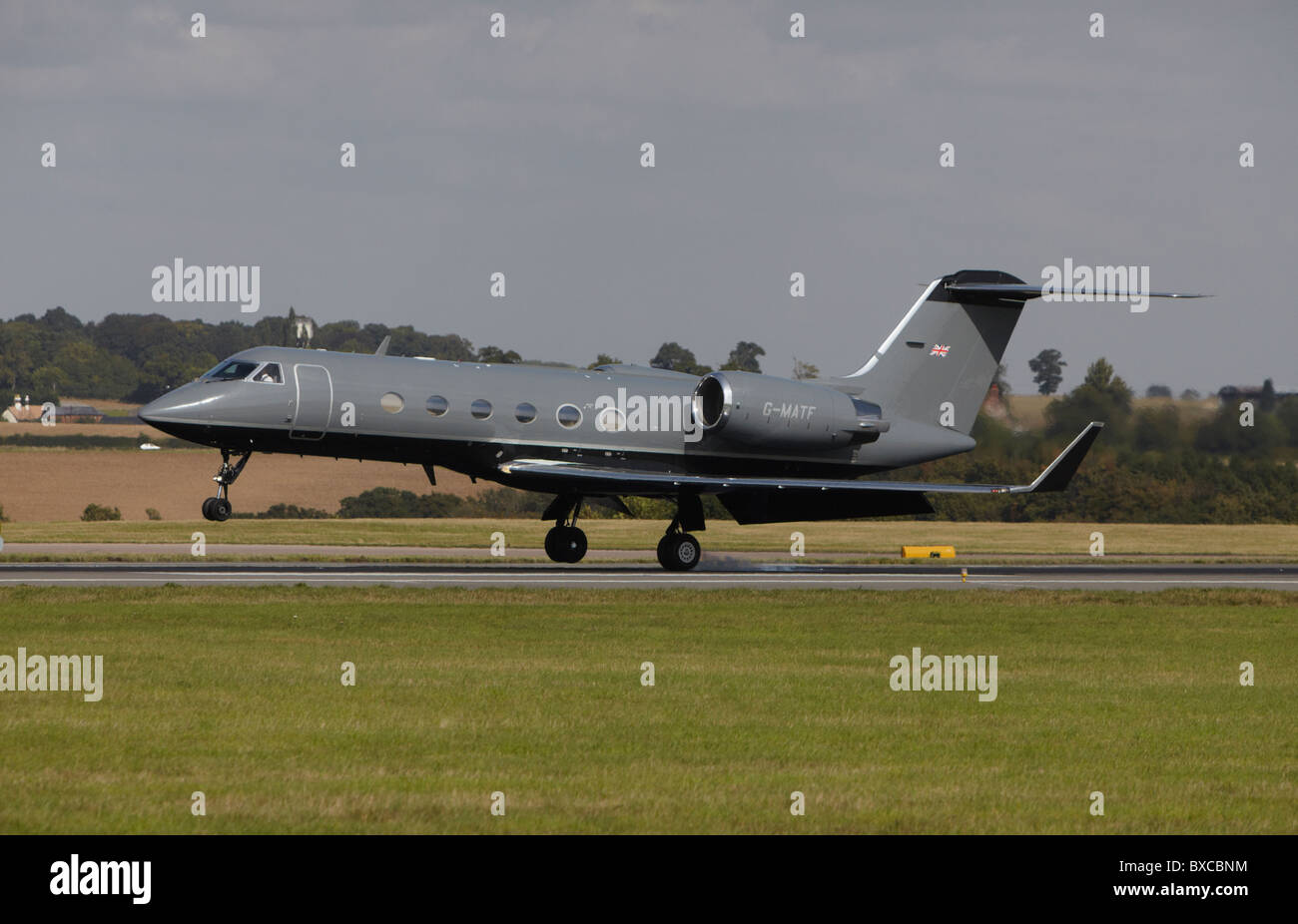 Gulfstream G-IV landing with smoke coming off tire at Luton Airport, Bedfordshire, England, United Kingdom - Stock Image