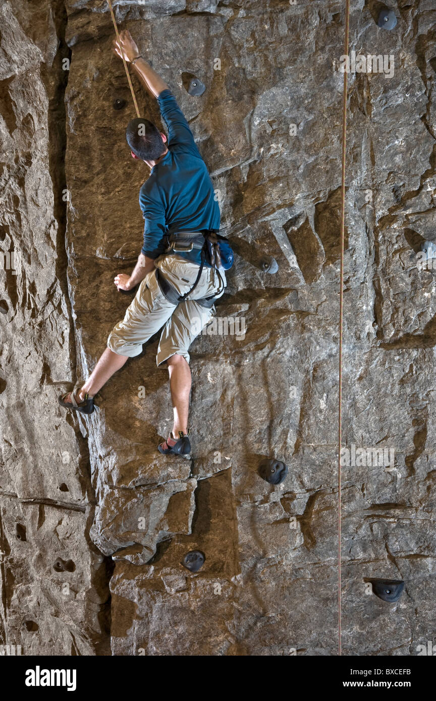 Rock Climber Climbing Indoor Rock Wall - Stock Image
