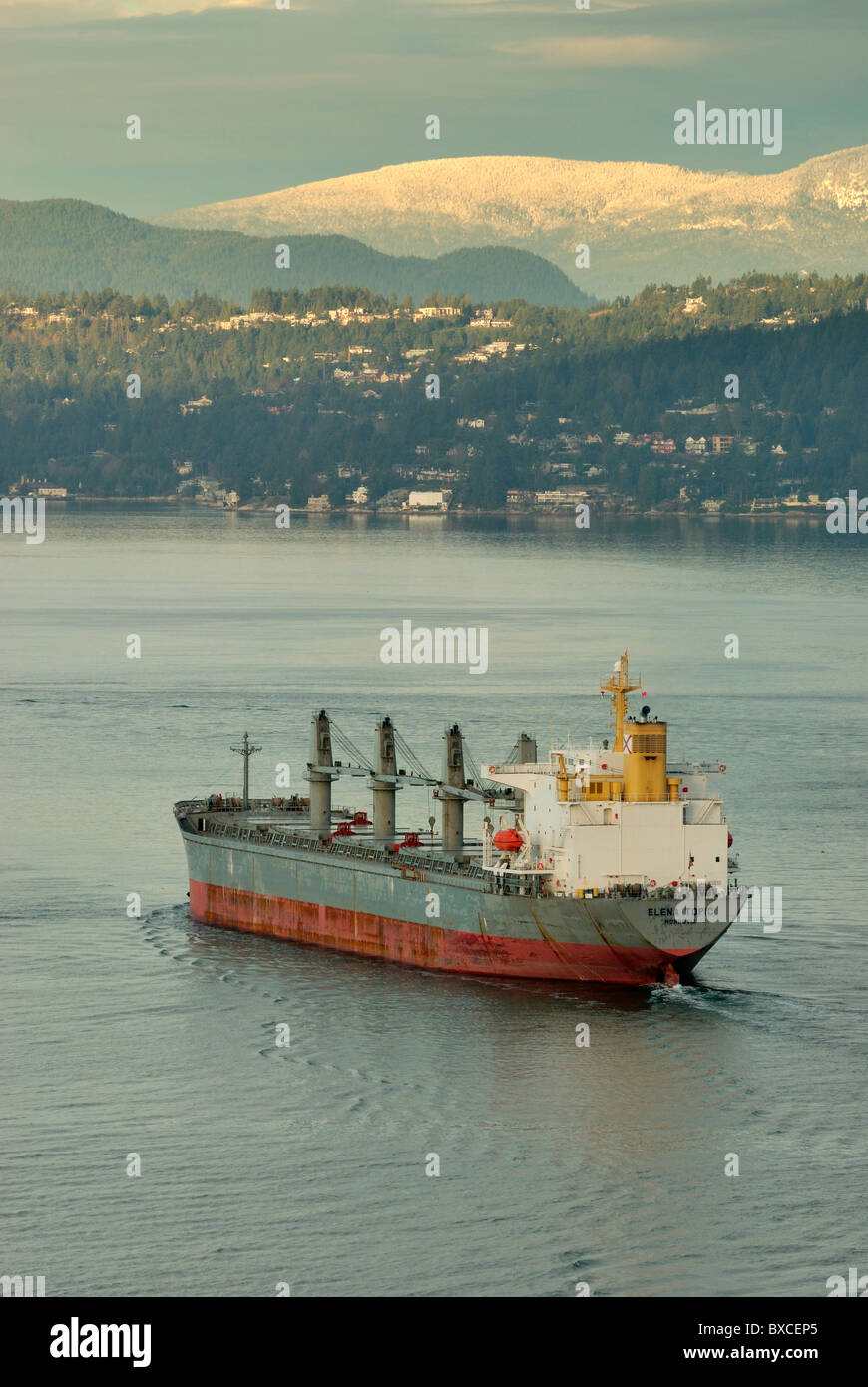 On a winter morning, Cargo Freighter Elena Topic departing Vancouver Harbor with West Vancouver in the background. - Stock Image