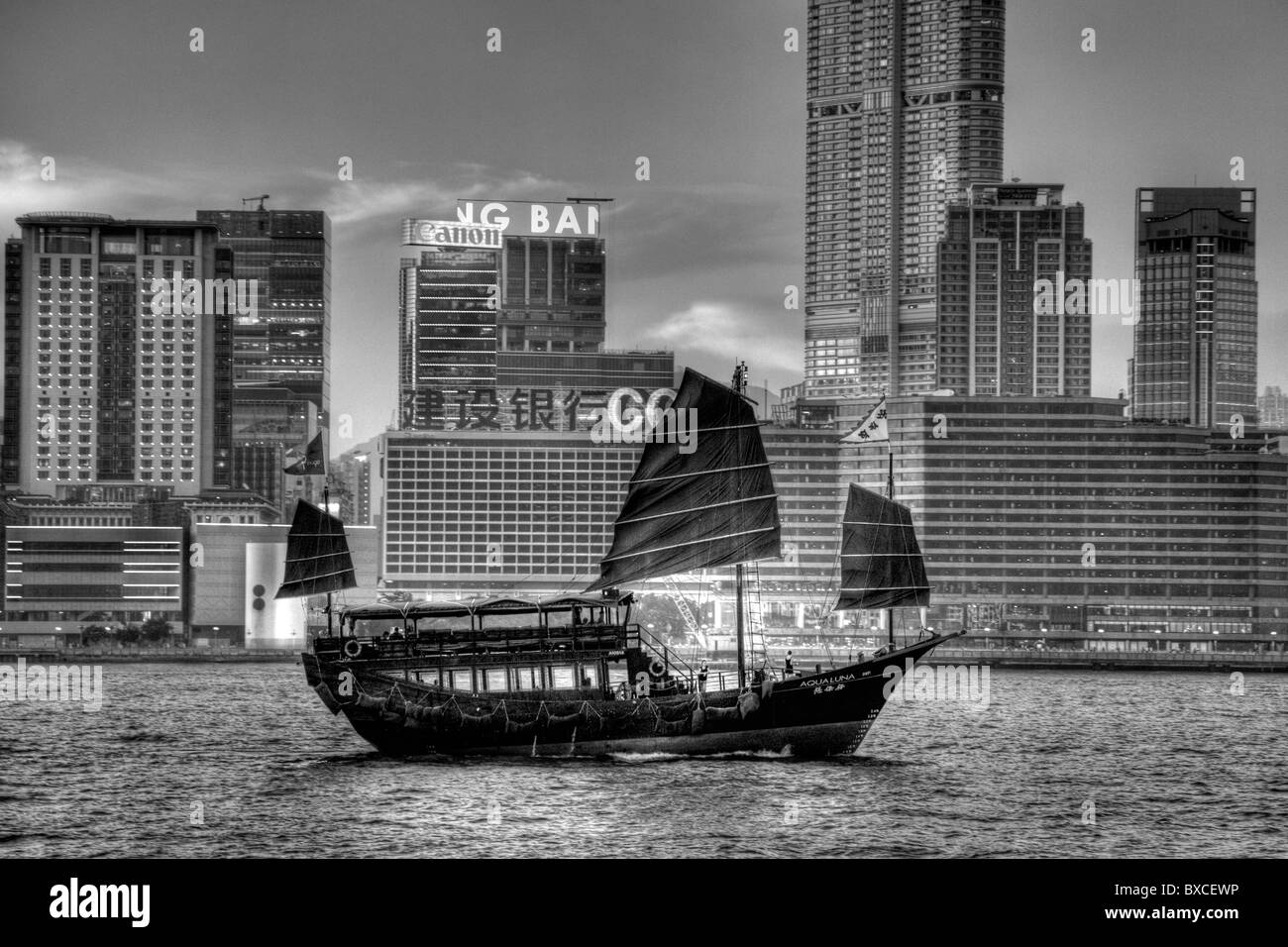 Hong Kong Junk Trips on Victoria Harbour, Harbor, with Kowloon in the background bat wing sails iconic sight - Stock Image