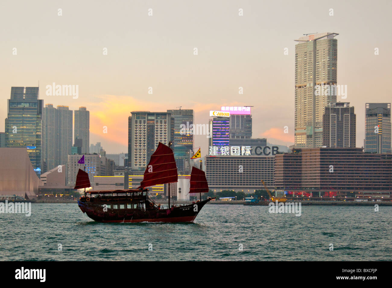 Hong Kong Junk Trips, on Victoria Harbour harbor with Kowloon skyline in the background iconic sight - Stock Image