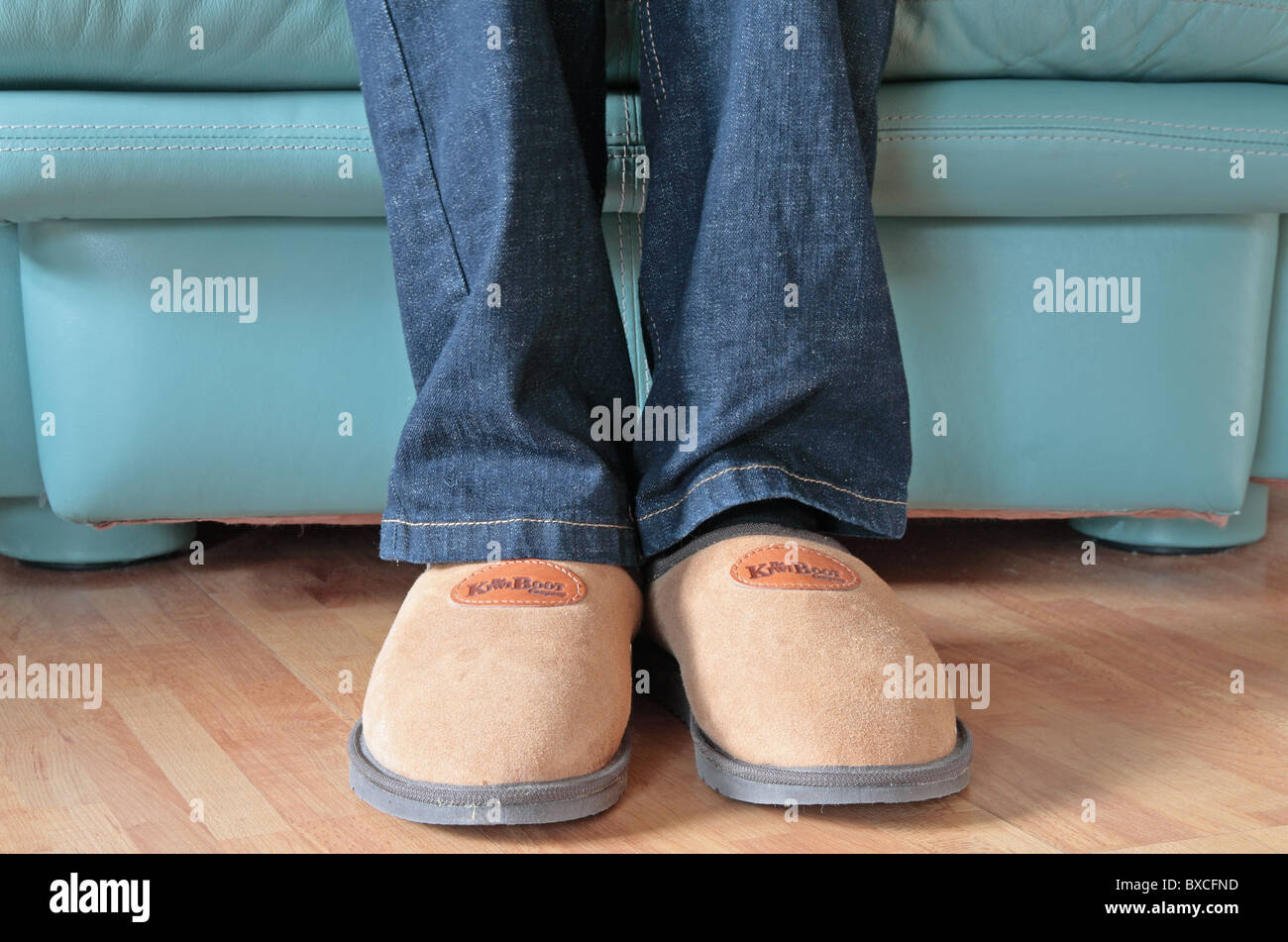 Man Wearing Sheepskin Comfy Slippers Whilst Sitting Down in a Leather Armchair MODEL RELEASED - Stock Image