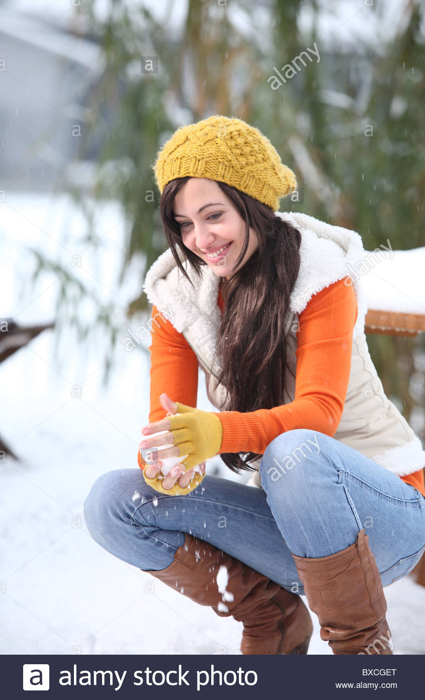 woman throwing snowball - Stock Image