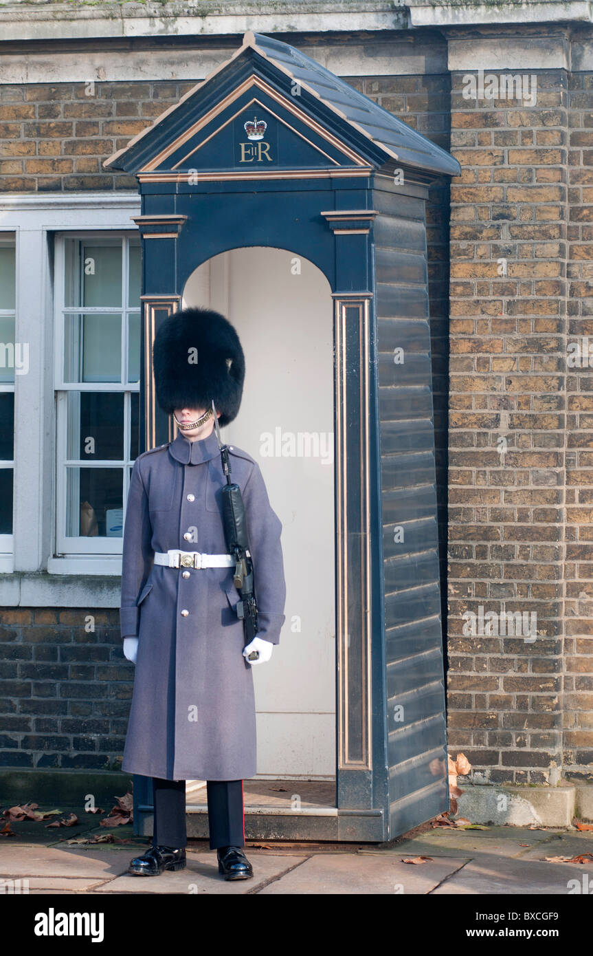 dcff821c145 Queens Guard in long grey tunic coat and Busby hat with fixed bayonet  standing guard outside