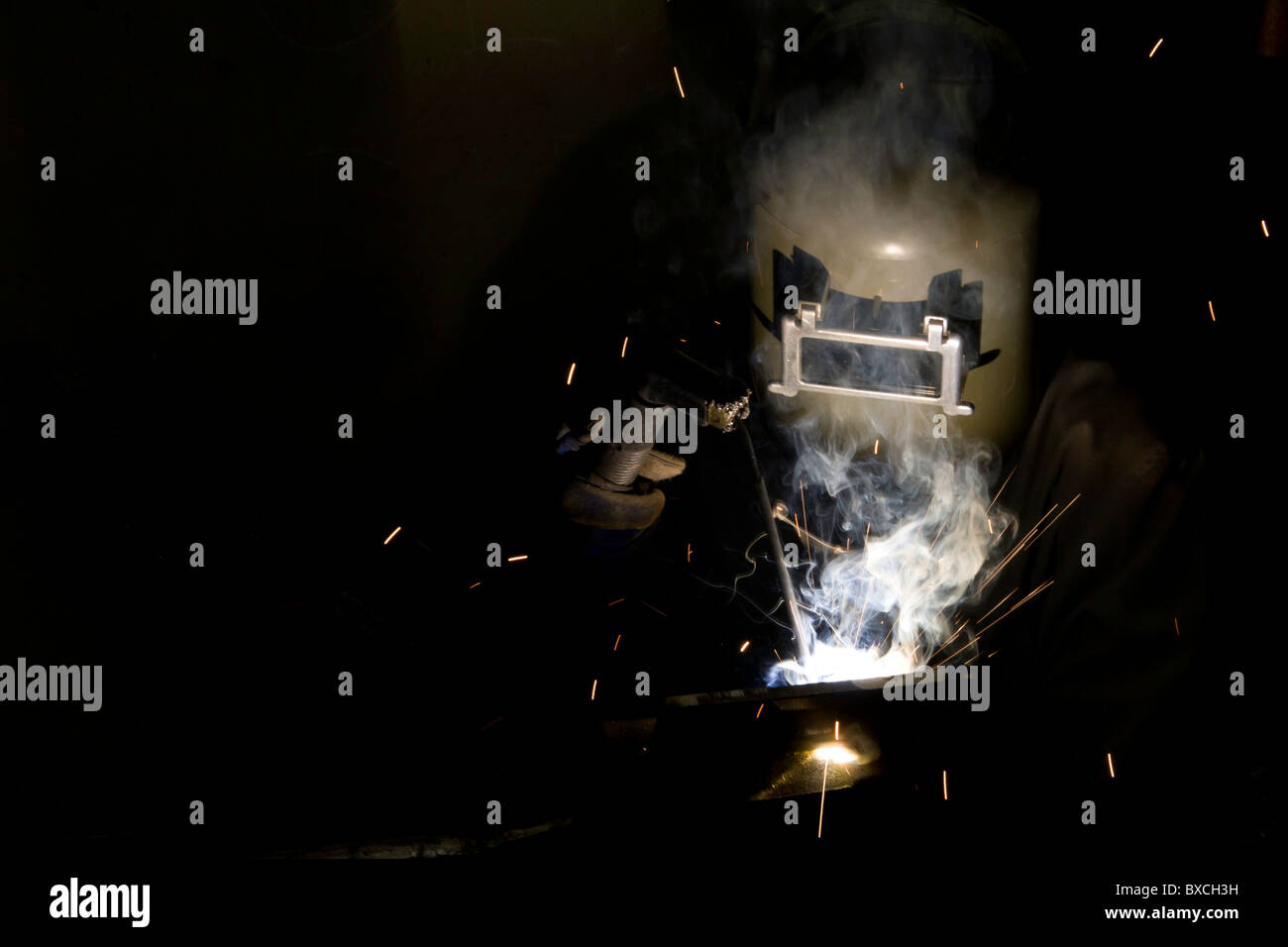Welder lit up by welding flash, background shrouded in darkness. Good ad copy space. - Stock Image