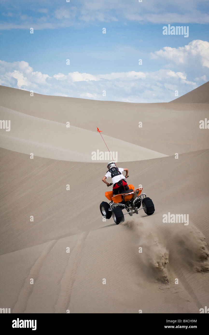 Teen riding ATV in sand dunes. Small jump over hill - Stock Image