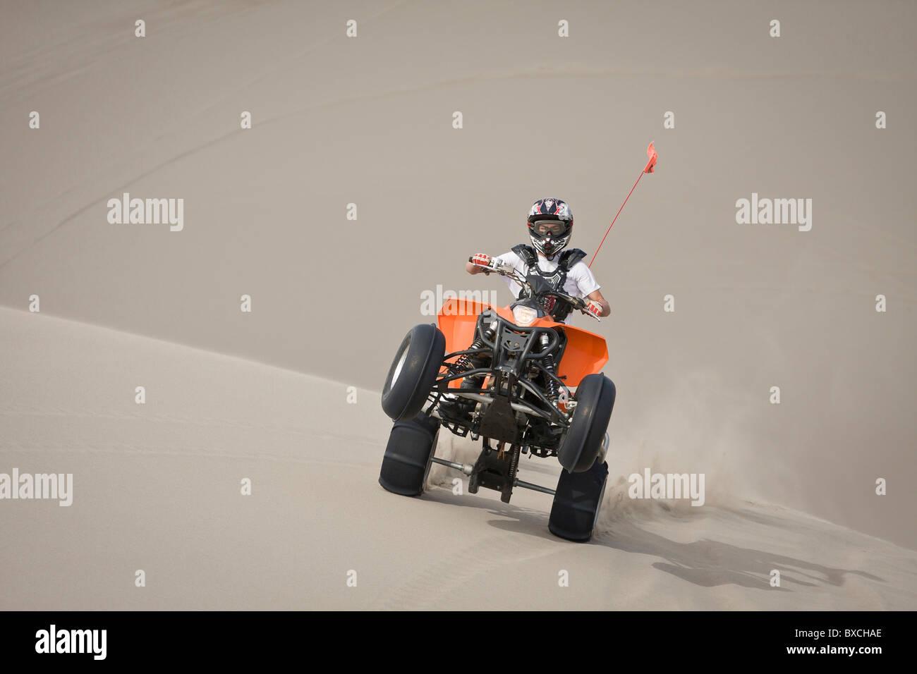 Teen boy riding ATV in sand dunes pulling a wheelie - Stock Image