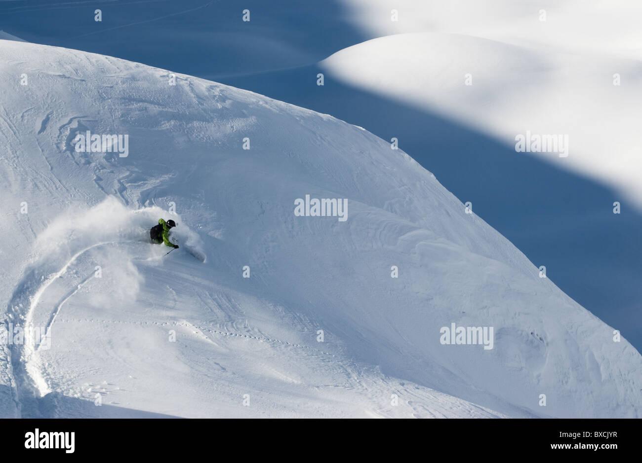 Telemark skier making a turn in powder snow on rugged terrain in Andermatt, Switzerland. - Stock Image