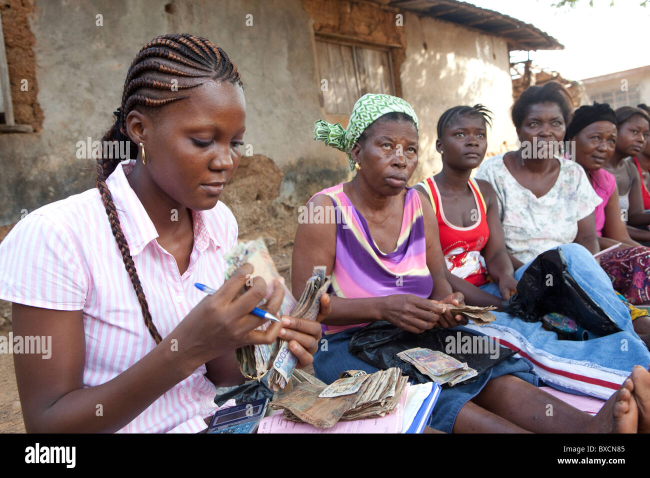 Women count cash after receiving microfinance loans in Freetown, Sierra Leone, West Africa. - Stock Image
