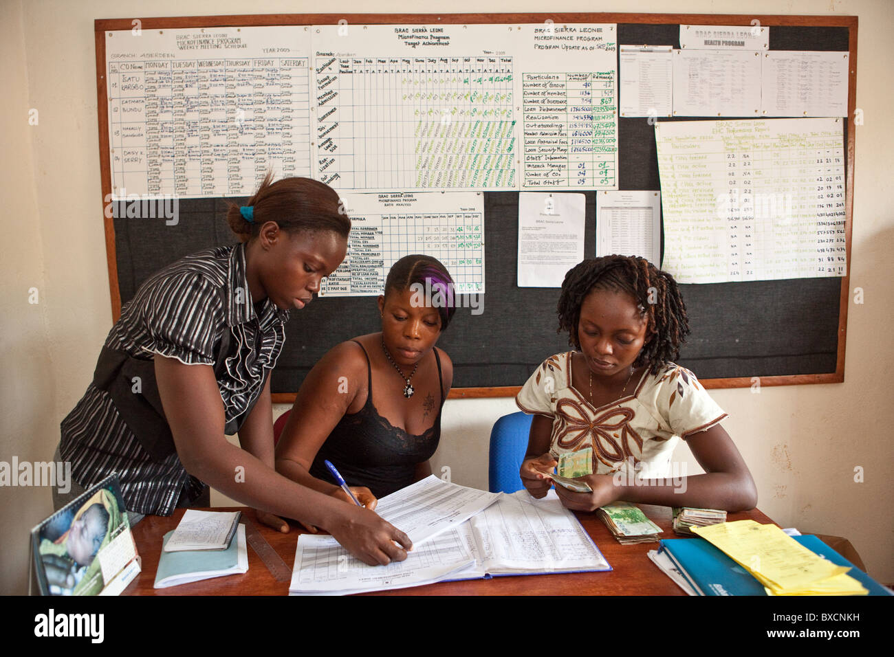 A woman signs for a microfinance loan in an office in Freetown, Sierra Leone, West Africa. - Stock Image
