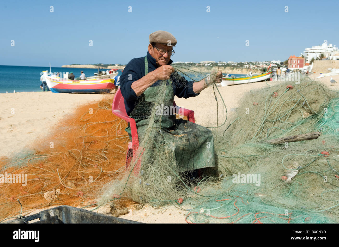 A fisherman on the beach, Armacao de Pera, Portugal - Stock Image