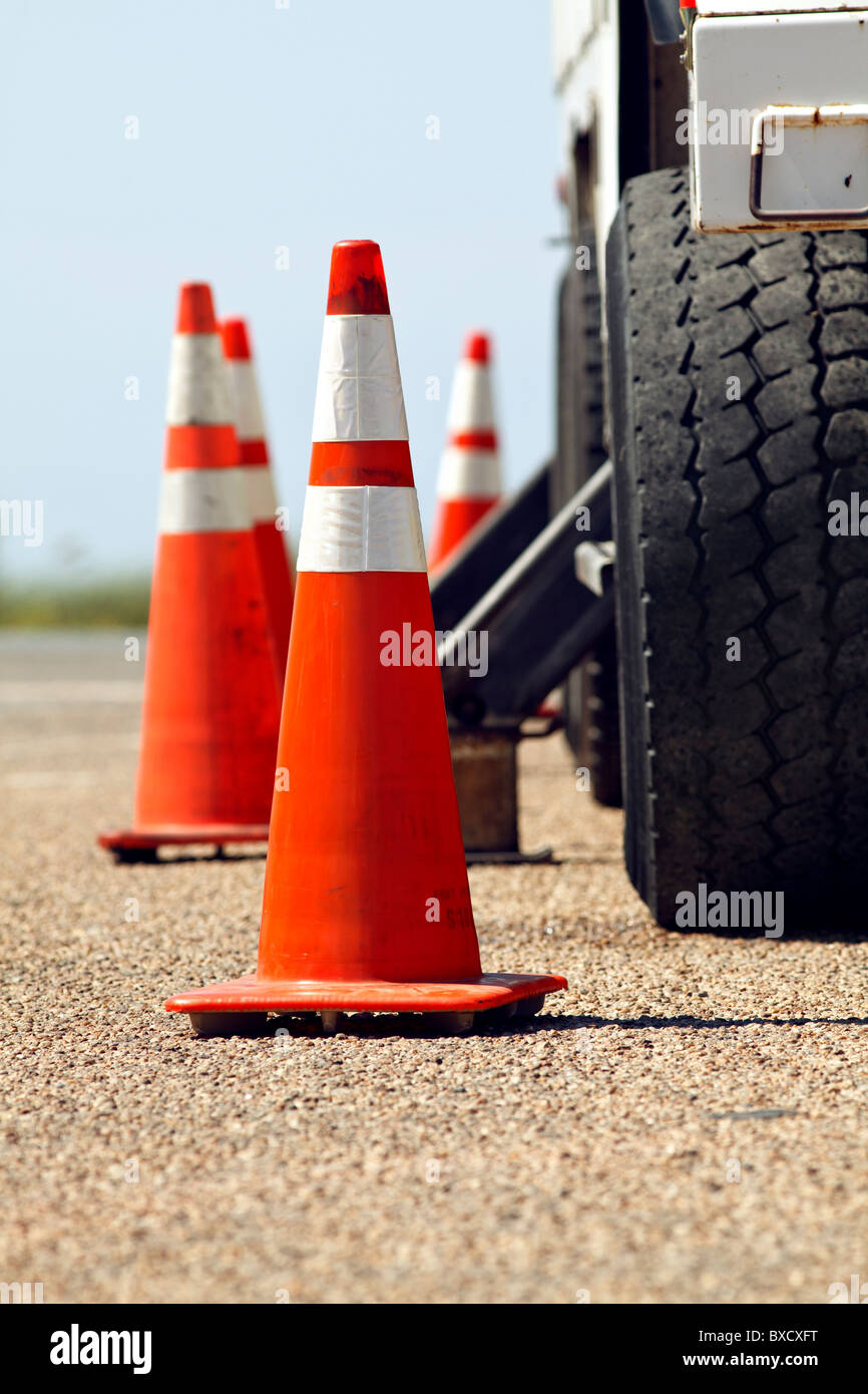 Orange, traffic cones around a utility truck parked on the street. - Stock Image