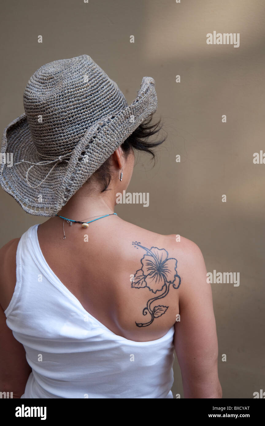 Hibiscus Flower Tattoo On The Shoulder Of A Young Woman In A White