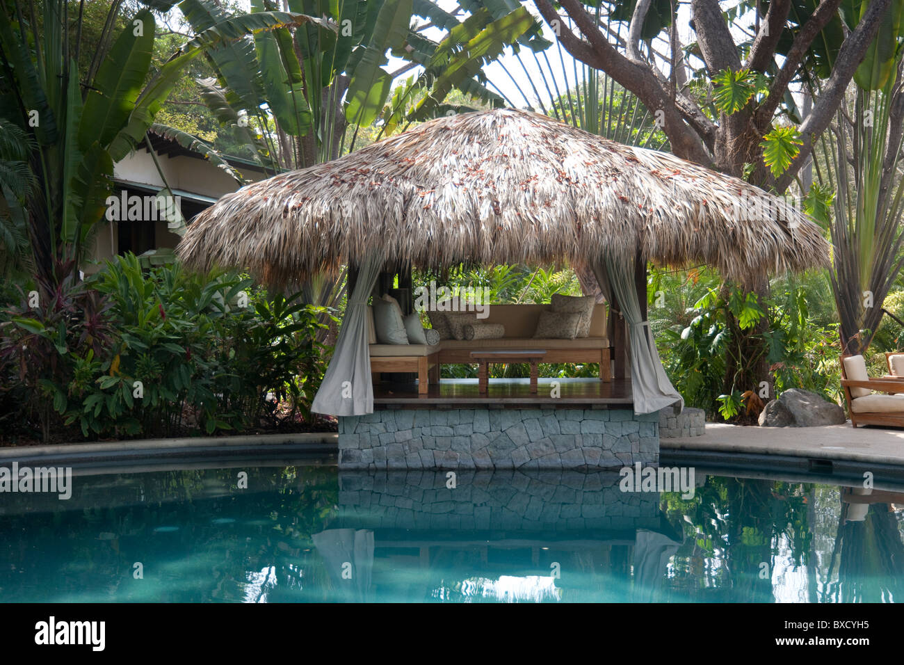 Open Sided Poolside Cabana With Palm Leaf Roof And Sofa Lounge