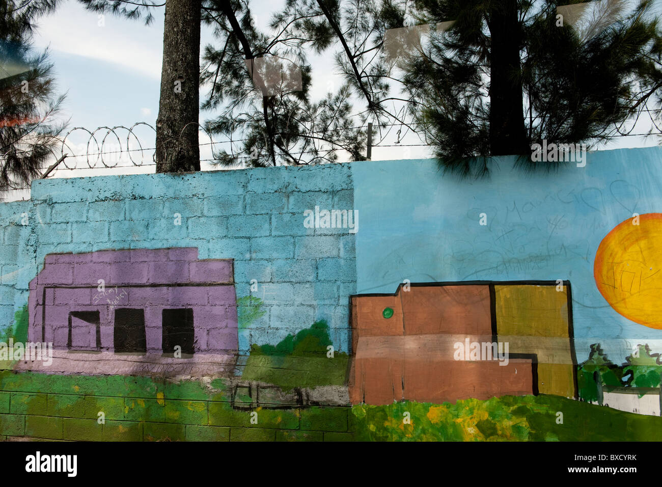 Painting of houses and buildings on concrete cinderblock wall, with ...