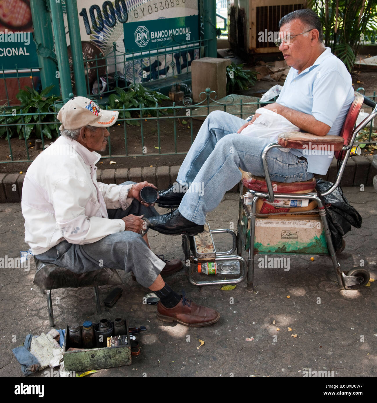 Man getting his shoes shined in San Jose Costa Rica - Stock Image