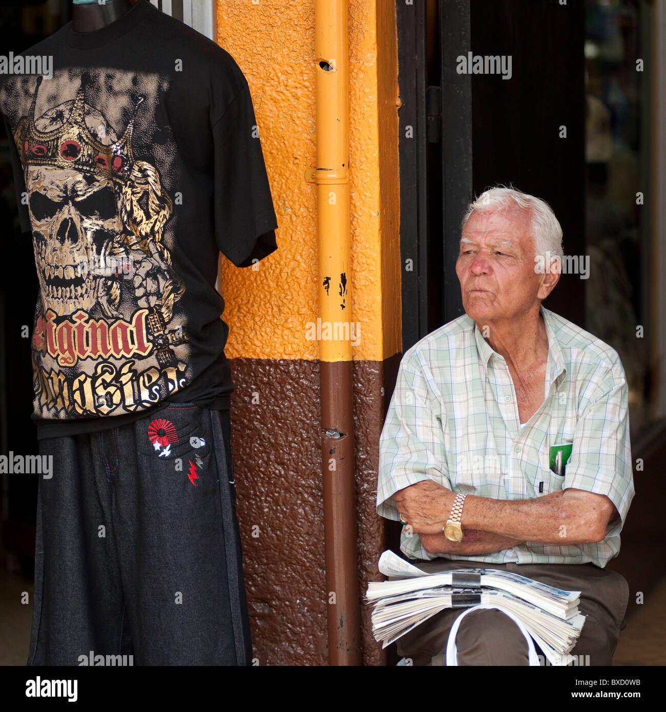 Man sitting in front of a store in San Jose Costa Rica - Stock Image