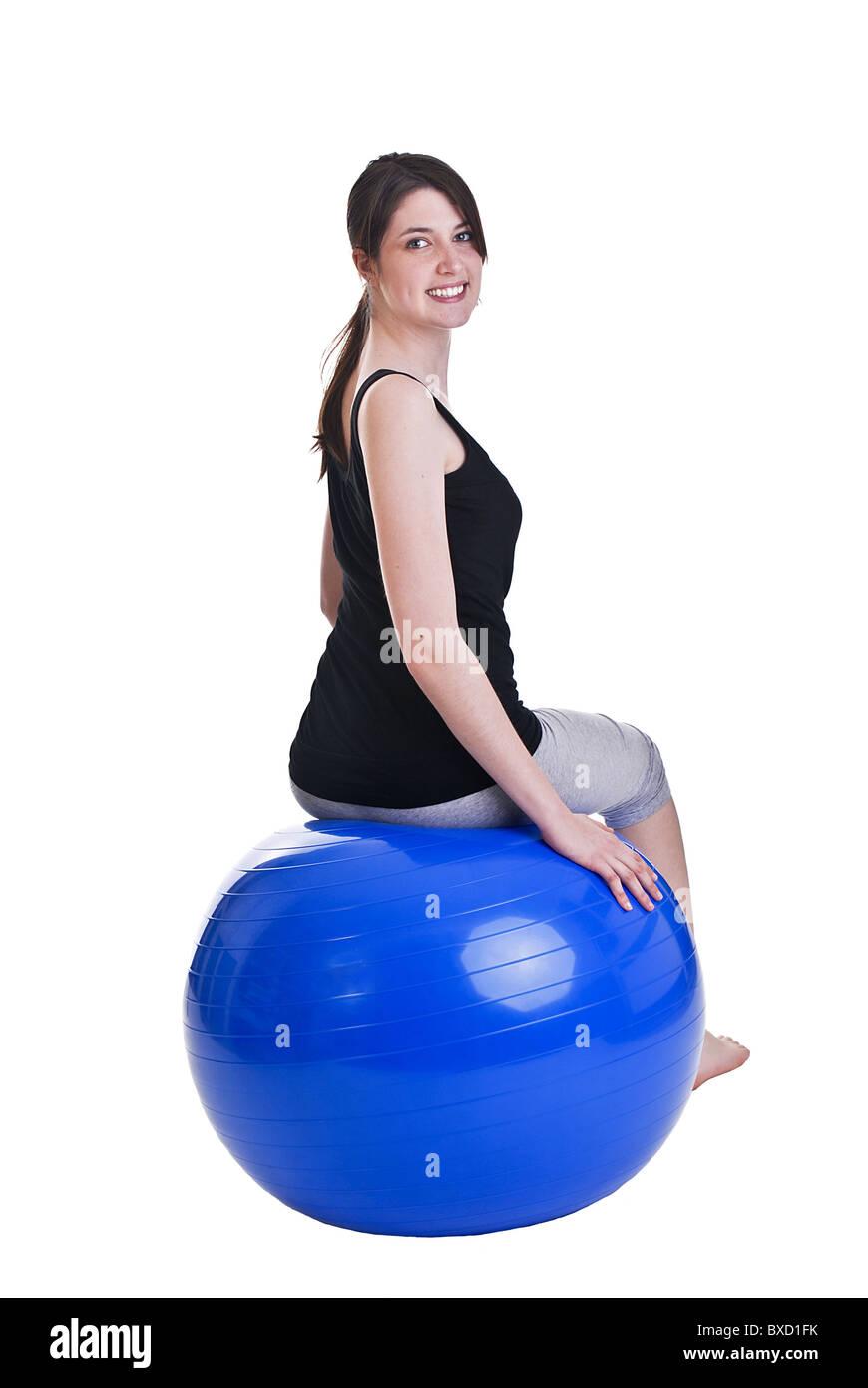 Young woman sitting on gymnastics ball - Stock Image