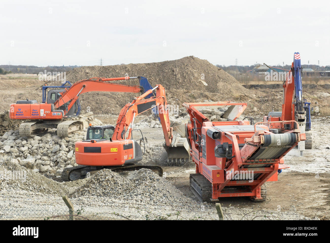 Excavator clearing a demolished site with an aggregate Crusher to make way for a paper recycling plant in Kings - Stock Image